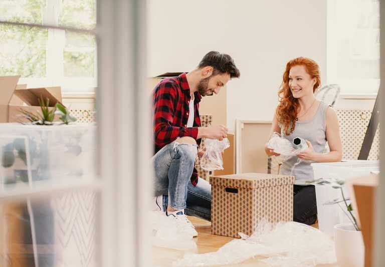 Smiling woman and man packing stuff while moving out from home